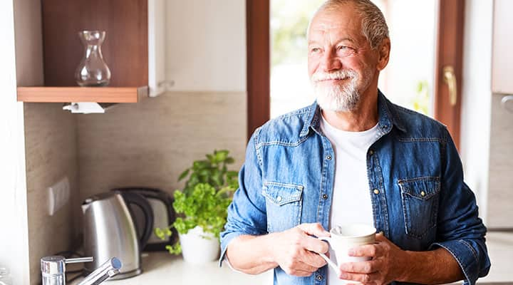 Older man standing in kitchen with more energy