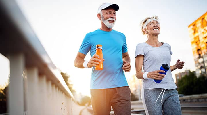 Older couple exercising outside for benefit