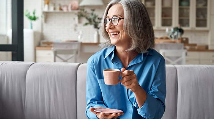 Woman laughing while enjoying cup of coffee