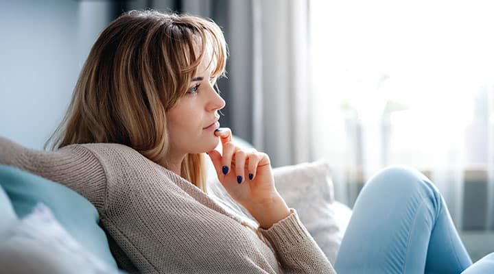 Woman sitting on couch thinking of starting the MIND diet