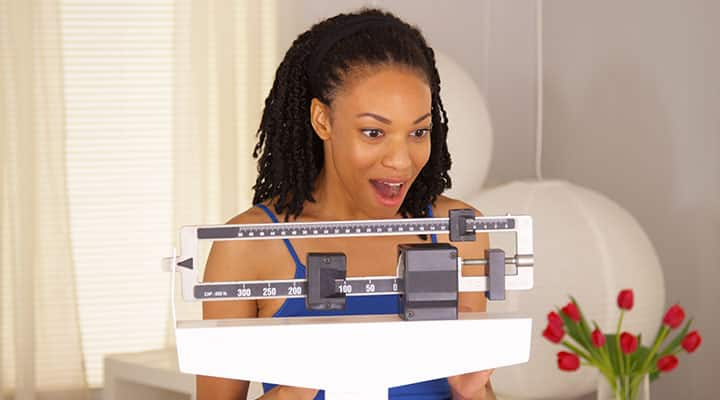 Woman on scale excited about her weight loss