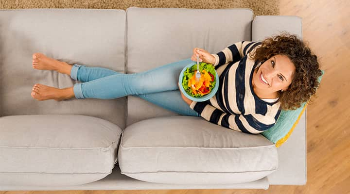 Woman on couch enjoying MIND-friendly meal