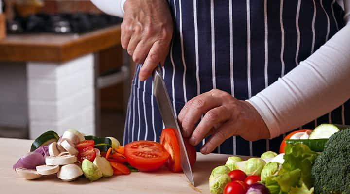 Man preparing vegetables for a sautéed veggie bowl