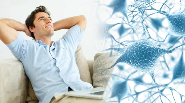 Man with laptop relaxing on couch with hands behind head