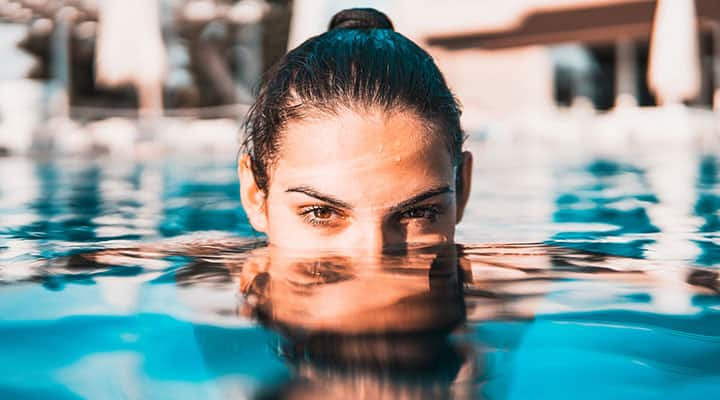 Woman in pool using serums to keep skin youthful