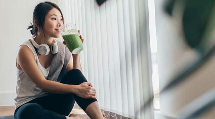Woman drinking green smoothie to fuel energy after workout