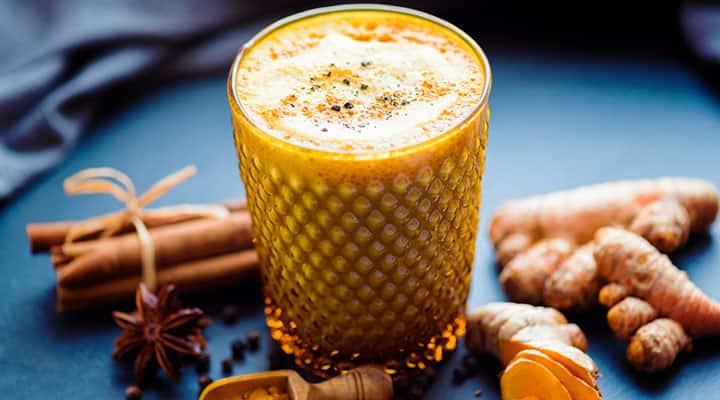 Glass cup of tumeric milk latte