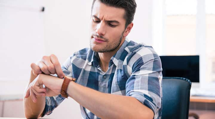 Man setting his wrist watch to better his concentration in alloted time