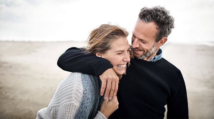 Couple on beach laughing away stress