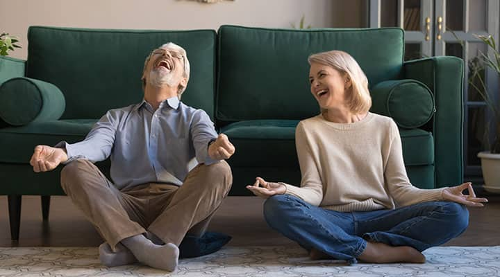 Couple laughing at each other while doing yoga