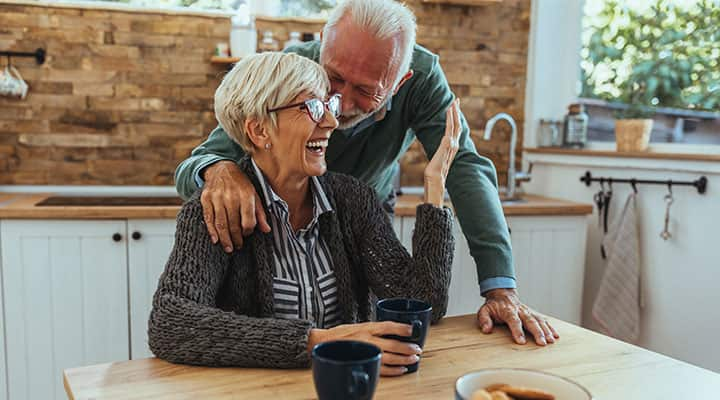 Senior couple laughing at table