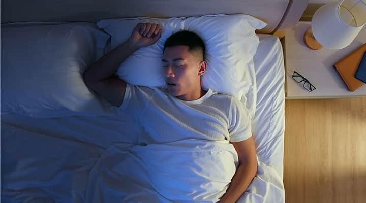 Man in bed experiencing REM sleep