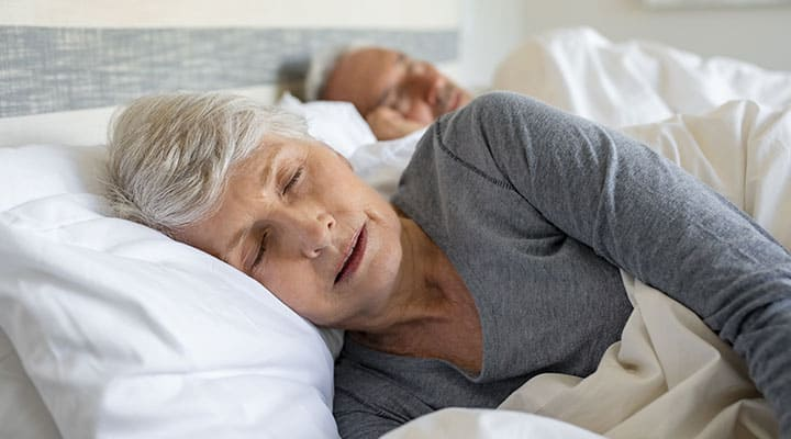 Older couple in bed going through the 4 stage of sleep