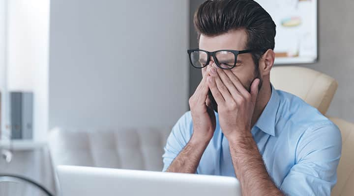 Man tired at desk due to lack of REM sleep