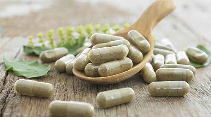 L-theanine capsules sitting in and near wooden spoon