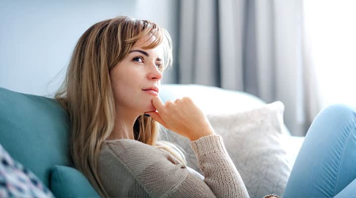 Woman in deep positive thoughts sitting on a couch