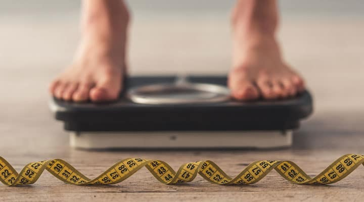 Man on scale to check body weight and body fat