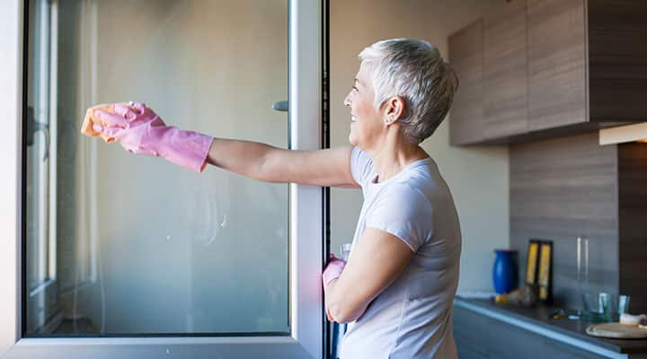Elderly woman cleaning kitchen window