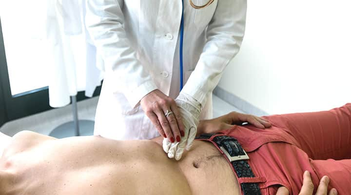 Man having doctor palpating liver for health