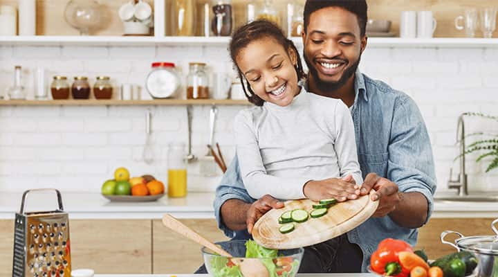 Father and daughter preparing healthy salad together