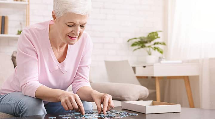 Older woman sitting on couch completing puzzle