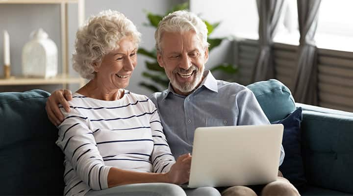 Older couple researching cognitive health on computer