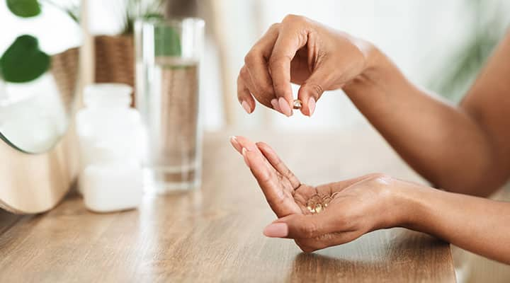 Woman holding pregnenolone capsule in her hand