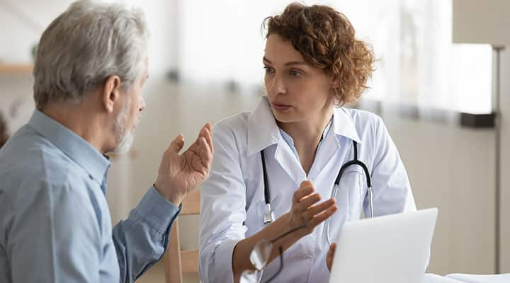 Older man talking with doctor about incorporating pregnenolone