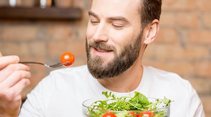Man eating salad slowly to avoid bloating