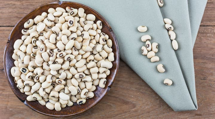 White kidney beans in a bowl on wooden surface