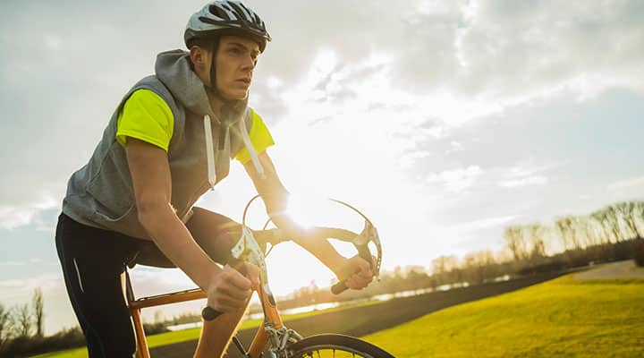 Man wearing t-shirt while cycling for better vitamin d3 absorption