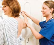 Technician with patient getting mammogram