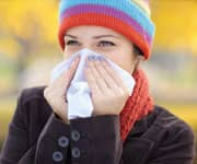 Woman with tissue having flu or allergy