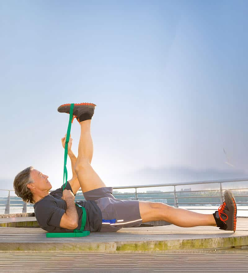 Man outdoors doing leg extensions with elastic band