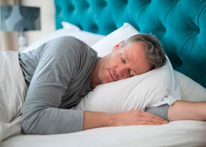 Man on bed sleeping with his left arm under the pillow
