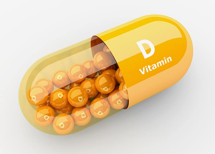 3d yellow pill with little capsule vitamind d inside